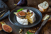 Camembert cheese with fresh figs, honey, walnuts and raisins on a rustic vintage wooden table. Dark and moody.