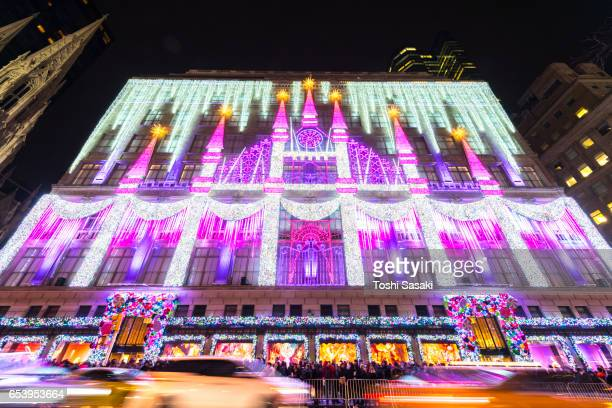 Camera captures 2016 Saks Fifth Avenue Holiday Light Show and crowd at front of Saks Fifth Avenue window displays, which are illuminated at night in Midtown Manhattan. Cars run on 5th Avenue at front of Saks Fifth Avenue.