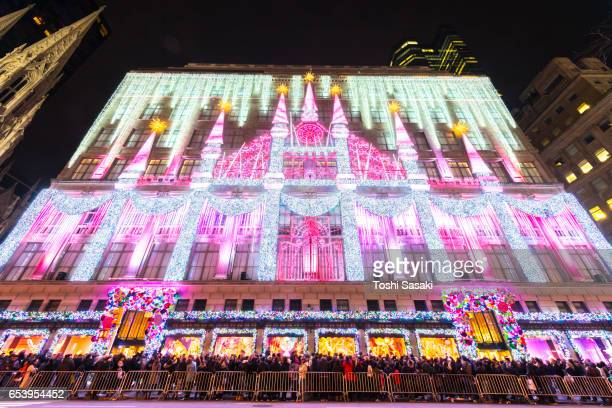 Camera captures 2016 Saks Fifth Avenue Holiday Light Show and crowd at front of Saks Fifth Avenue window displays, which are illuminated at night in Midtown Manhattan.