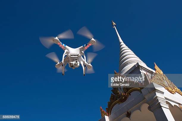 A camera equipped radio controlled quadcopter drone flying over a Buddhist shrine in Phu Ruea National Park in northern province of Loei in Thailand