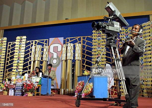 A camera man films contestants answering trivia questions during the taping of Afghanistan's most popular game show 'Test Your Brain' or 'Azmonga...