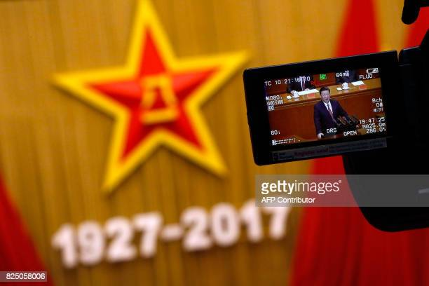 A camera monitor shows China's President Xi Jinping speaking during a ceremony to commemorate the 90th anniversary of the founding of the People's...