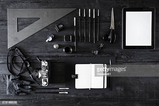 Camera, note book, digital tablet and tools on black wood