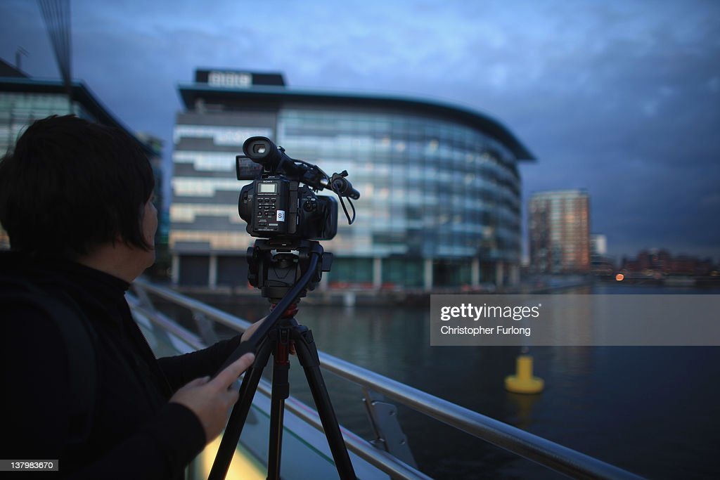 A camera operator films outside the BBC studios at Media City on January 30, 2012 in Salford, England. The BBC is soon to be joined by new neighbour ITV Granada and the cobbled streets of ITV soap opera 'Coronation Street'. The new ITV complex is being built on the banks of Manchester Ship Canal opposite the BBC in Media City.