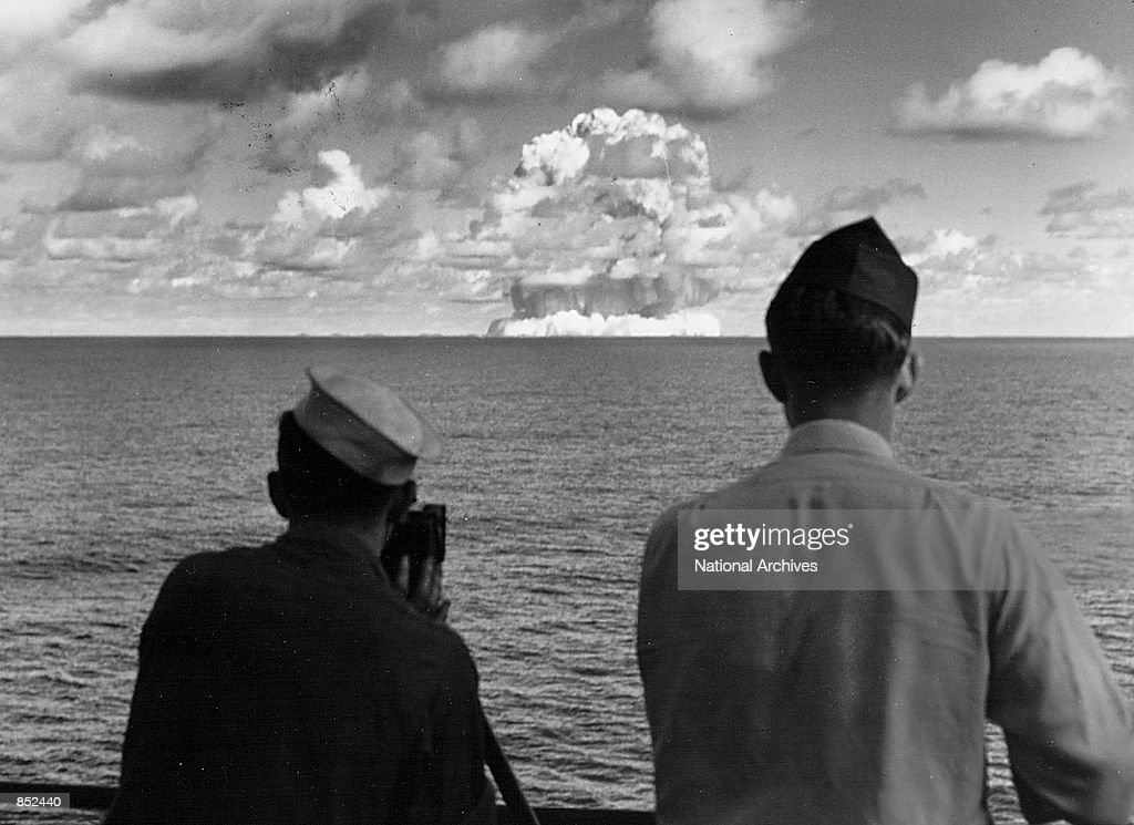 Camera personel aboard the USS Mt. McKinley watch an atomic cloud July 25, 1946 during the 'Baker Day' blast at Bikini Island.