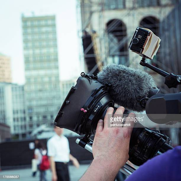 Cameraman at work holding his camera with his left hand