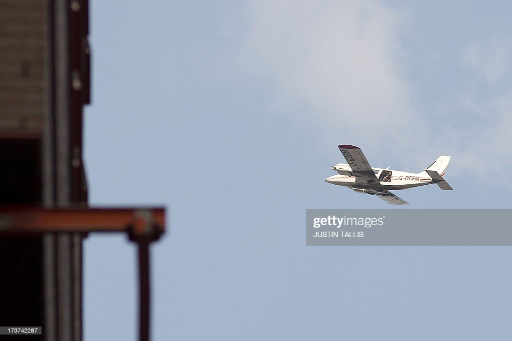 A cameraman captures footage from a plane flying above the Lindo Wing of Saint Mary's Hospital in London, on July 17, 2013, where Prince William and his wife Catherine's baby will be born. Queen Elizabeth II, it seems, is just as impatient as her subjects for the royal baby to arrive this week -- because she is going on holiday.