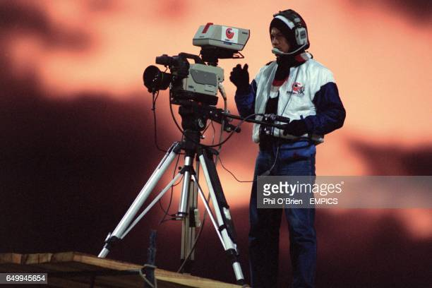 TV Cameraman covering the match with red sky behind him
