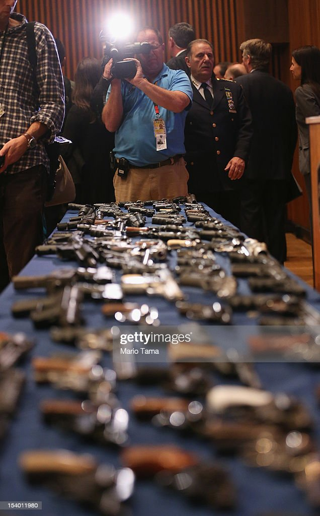 A cameraman documents a table of illegal firearms sold to undercover officers in a large weapons bust in East Harlem following a press conference on October 12, 2012 in New York City. NYPD detectives arrested 13 suspects for the illegal sale of 129 guns mostly purchased from gun dealers and pawn shops in South Carolina.