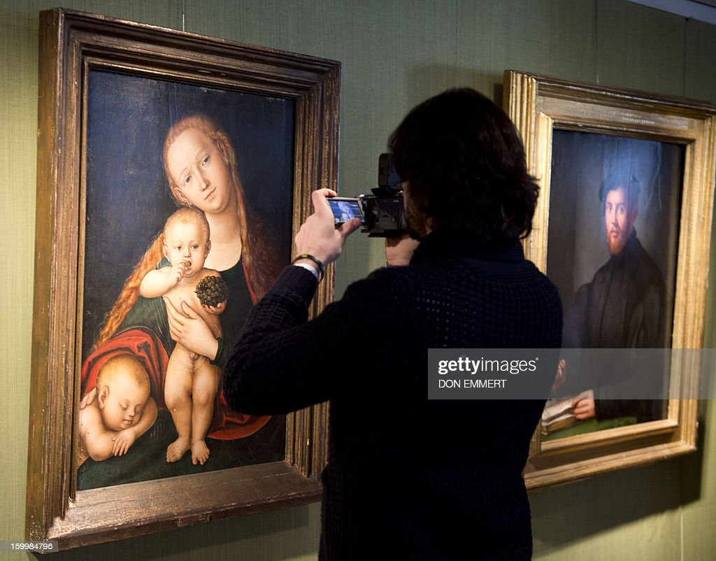 A cameraman does a closeup of 'The Virgin and Child with Infant' by Lucas Cranach II January 24, 2013 at Christie's in New York. The painting is one of the works scheduled to be auctioned during Old Masters week January 26-31, 2013.