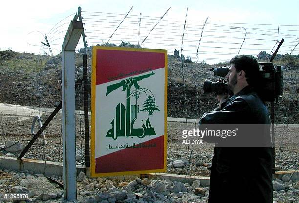 A cameraman films 17 November 2000 a logo of Hezbollah placed at Hassan gate in Shebaa farms a disputed area on the LebaneseSyrian borders occupied...