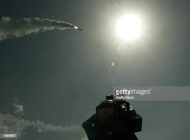 A cameraman films a Tomahawk cruise missile as it flies toward Iraq after being launched from the AEGIS guided missile cruiser USS San Jacinto March...