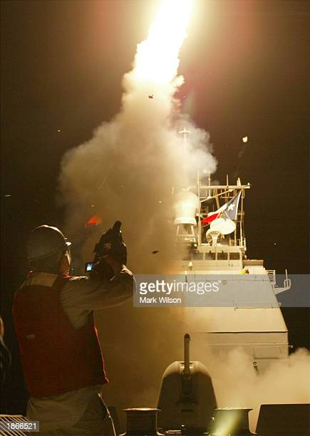 A cameraman films a Tomahawk cruise missile as it launches toward Iraq from the deck of the AEGIS guided missile cruiser USS San Jacinto March 21...