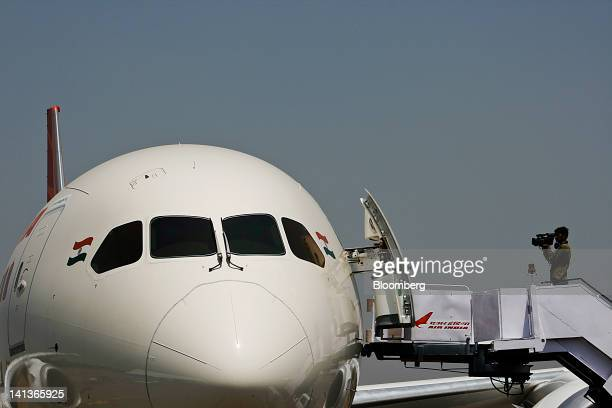 A cameraman films an Air India Ltd Boeing Co 787 Dreamliner displayed at the India Aviation 2012 conference at Begumpet Airport in Hyderabad India on...