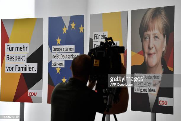 A cameraman films election posters of Germany's conservative Christian Democratic Union party showing among others the party's top candidate for...