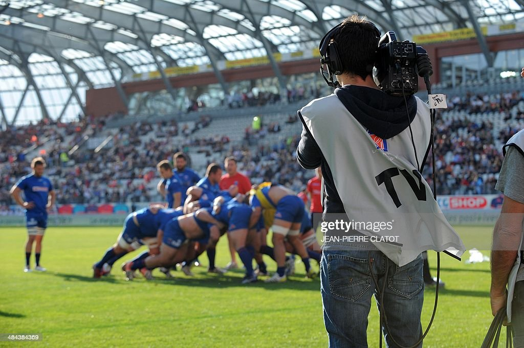 A cameraman films Grenoble's players as they warm up prior to the French Top 14 rugby union match between Grenoble (FCG) and Montpellier (MHR) on April 12, 2014 at the Stade des Alpes in Grenoble.