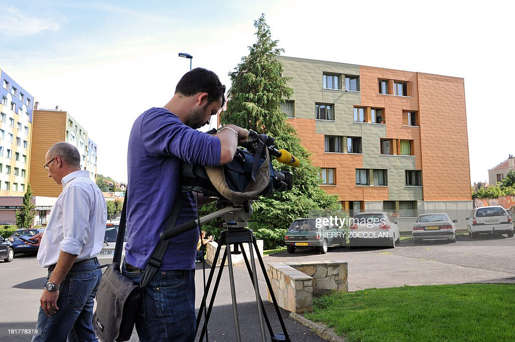 A cameraman films, on September 25, 2013 in Clermont-Ferrand, the building where lives the mother of Fiona, a five-year old girl who disappeared last May 12, as police officers proceed an investigation.