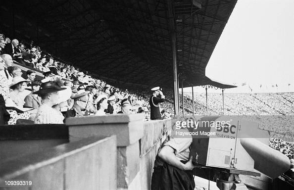 A BBC cameraman films proceedings at Wembley Stadium as King George VI salutes the march past of 6000 athletes at the opening ceremony of the Olympic...