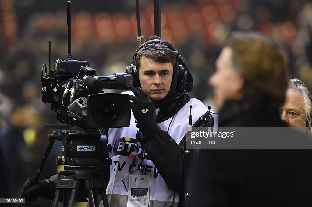 A cameraman films pundits at pitchside during the English Premier League football match between Liverpool and Tottenham Hotspur at the Anfield...