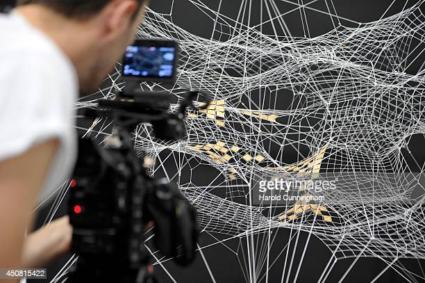 A cameraman films the artwork 'White net with wooden details working title' by Tomas Saraceno in the gallery section of Art Basel on June 18 2014 in...