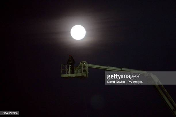 A cameraman films the game from above on a crane backlit by the moon