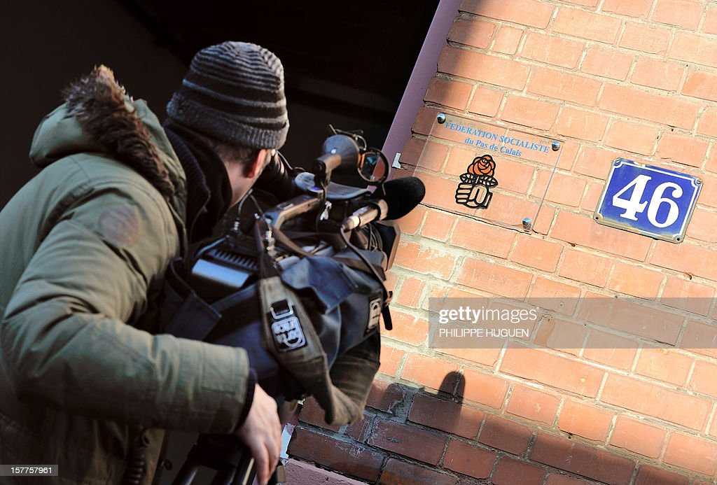 A cameraman films the headquarters of the French socialist party federation of the Pas-de-Calais on December 6, 2012 in Lens, during a search as part of an inquiry into an alleged hidden financing of this federation, involving local MP Jean-Pierre Kucheida.