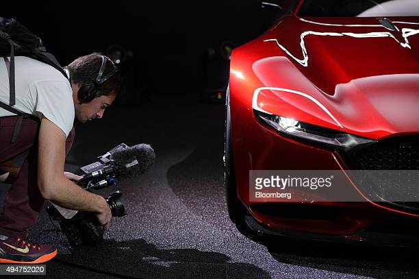 A cameraman films the hubcap of the Mazda Motor Corp RXVision concept vehicle on display at the Tokyo Motor Show in Tokyo Japan on Wednesday Oct 28...