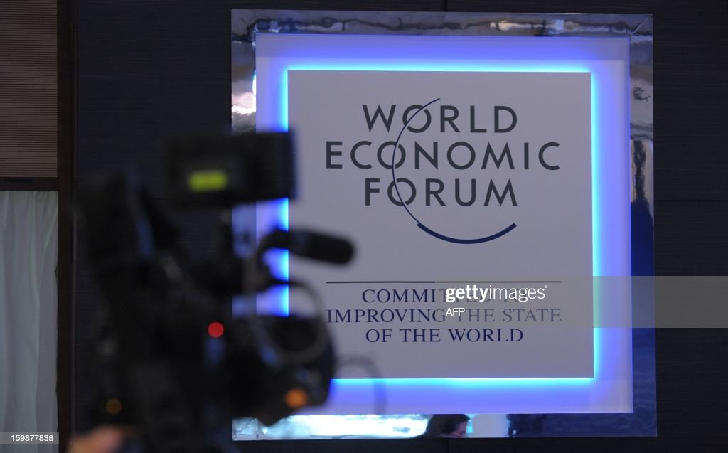 A cameraman films the plaque of the World Economic Forum at the congress center in Davos on January 22, 2013 prior to the opening of the World Economic Forum 2013 meeting. The meeting gathers some of the world's leading politicians and economists and is viewed as a global think tank forum.