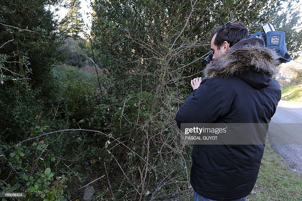 A cameraman films the scene on January 25, 2013 in Courbessac, where the semi-clothed body of the 34-year-old woman was found a day before after her children's school alerted her partner that she had failed to pick them up.
