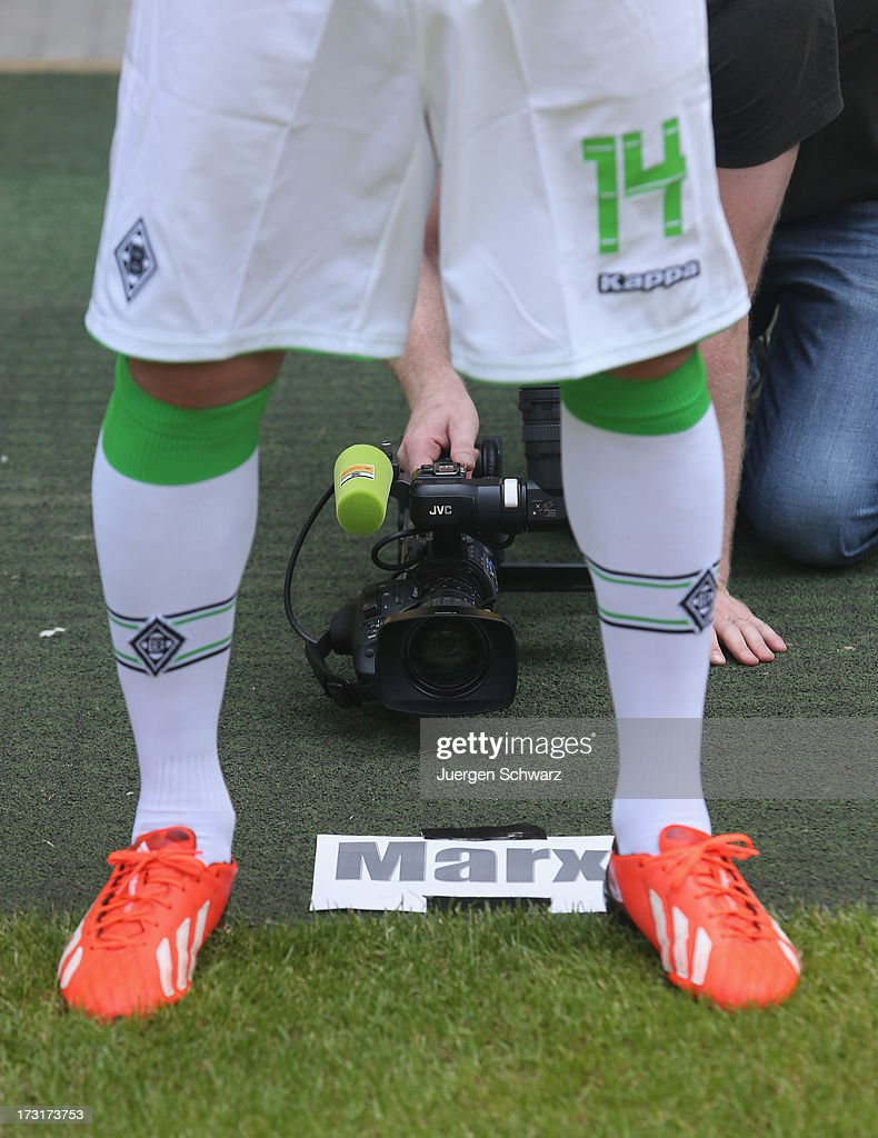 A cameraman knees behind Thorben Marx during the team presentation of Borussia Moenchengladbach on July 9, 2013 in Moenchengladbach, Germany.