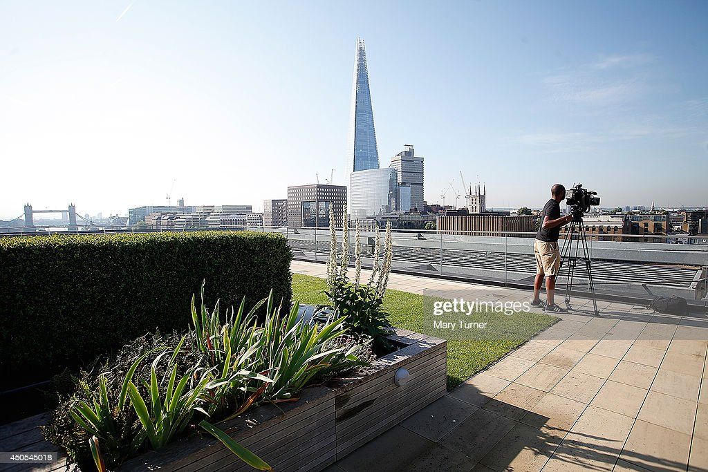 A cameraman looks out over The Thames from the Nomura rooftop gardens, which are opening to the public for the first time as part of Open Garden Squares Weekend 2014, on June 13, 2014 in London, England. Nomura's 6th floor terrace garden with panoramic views across the Thames is one of over 200 usually private gardens which members of the public will be able to explore between June 14th and 15th 2014.