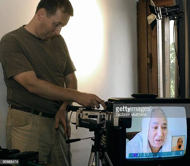 Cameraman of the British Broadcasting Corporation frames a Kashmiri woman talking to relatives inside a studio in Srinagar 23 June 2004 where the BBC...