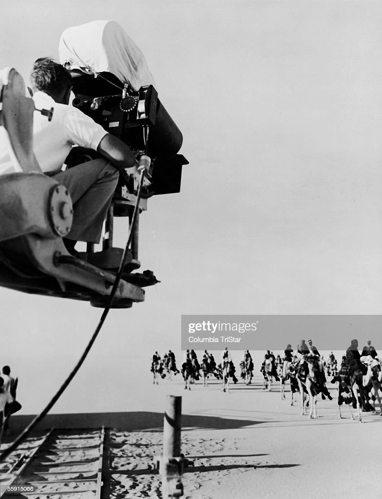 A cameraman on a crane films a shot of actors approaching on camels in a scene from the film 'Lawrence of Arabia,' directed by David Lean, 1962.