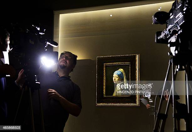 A cameraman prepares to film the masterpiece 'Girl with a Pearl Earring' by Dutch painter Johannes Vermeer during a preview of the exhibition 'The...