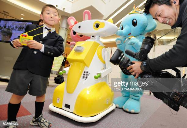 A TV cameraman shoots a kindergartner smiling with joy as a communication robot developed by Japan's robot maker 'tmsuk' calls his name at Aeon...