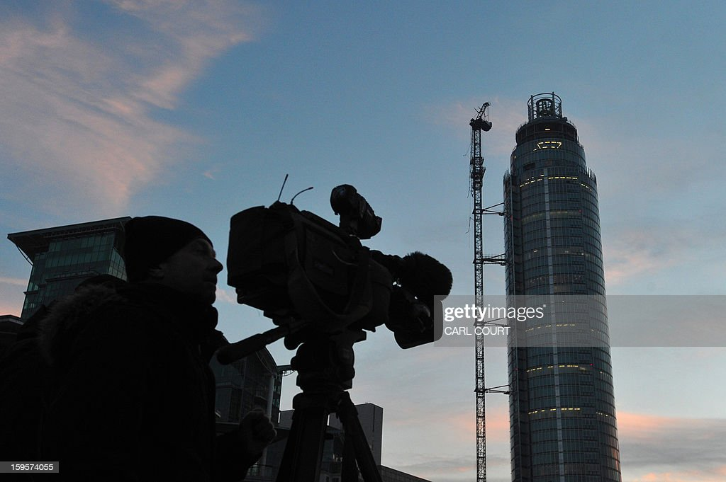 A cameraman take footage of The Tower at St George Wharf development, the scene of a helicopter crash, in central London on January 16, 2013. Two people were killed when a helicopter hit a crane at a building site in central London during morning rush hour and plunged to the ground in a ball of flames.