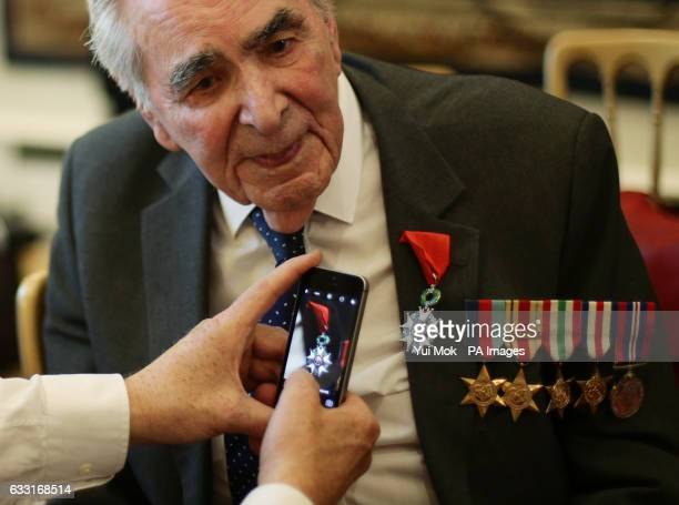 A cameraman takes a photos of Oliver LucasHodge from Bedfordshire Signalman in the Royal Navy during a ceremony for the Legion dOtildehonneur...
