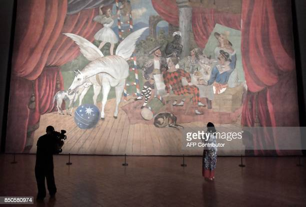 A cameraman takes a video of the artwork a monumental stage curtain for the ballet 'Parade' by Spanish artist Pablo Picasso during the press preview...