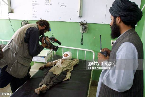 A CNN cameraman takes footage of a child said to have been wounded in a US bombing raid November 2 2001 in a hospital in Kandahar Afghanistan as a...