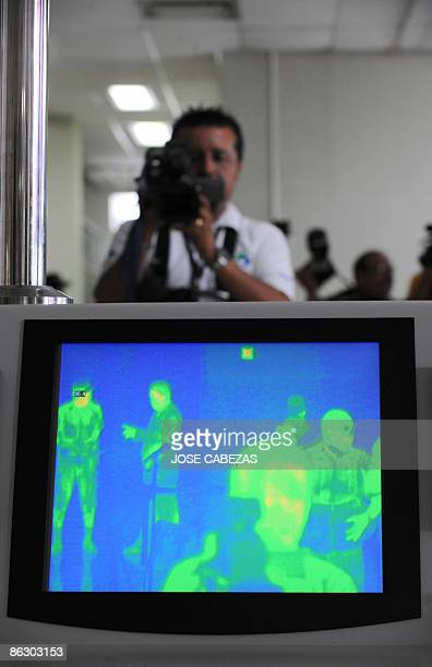 A TV cameraman takes images of a thermal scanner as people are scanned at El Salvador's International Airport in an effort to halt the spread of...