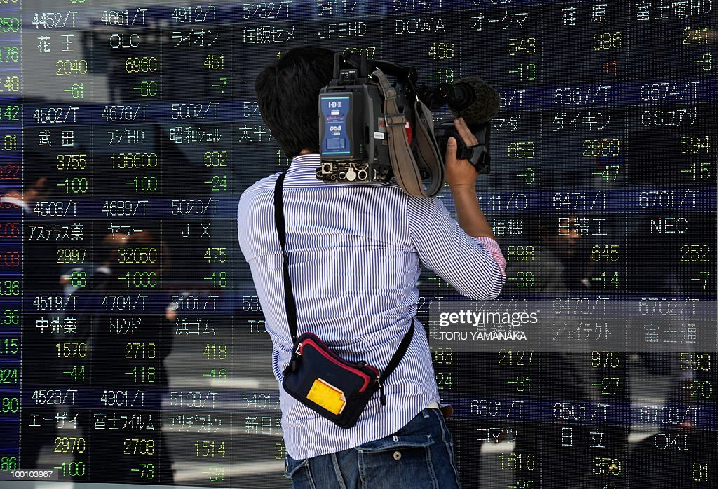 A TV cameraman takes video of an electric quotation board flashing share prices of the Tokyo Stock Exchange (TSE) in front of a securities company in Tokyo on May 21, 2010. Japanese shares plunged 2.51 percent by noon following Wall Street's biggest drop in more than a year and as the continued strength of the yen prompted investors to sell shares. AFP PHOTO/Toru YAMANAKA