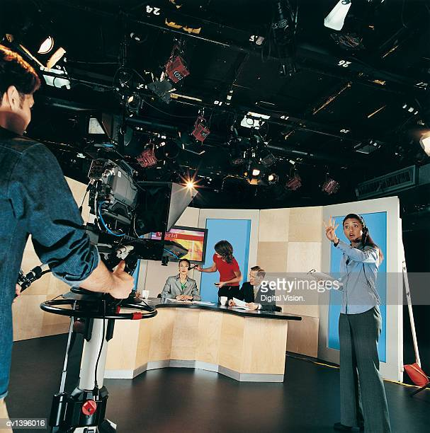 Cameraman, TV News Presenters and Behind the Scenes Crew in a TV Studio