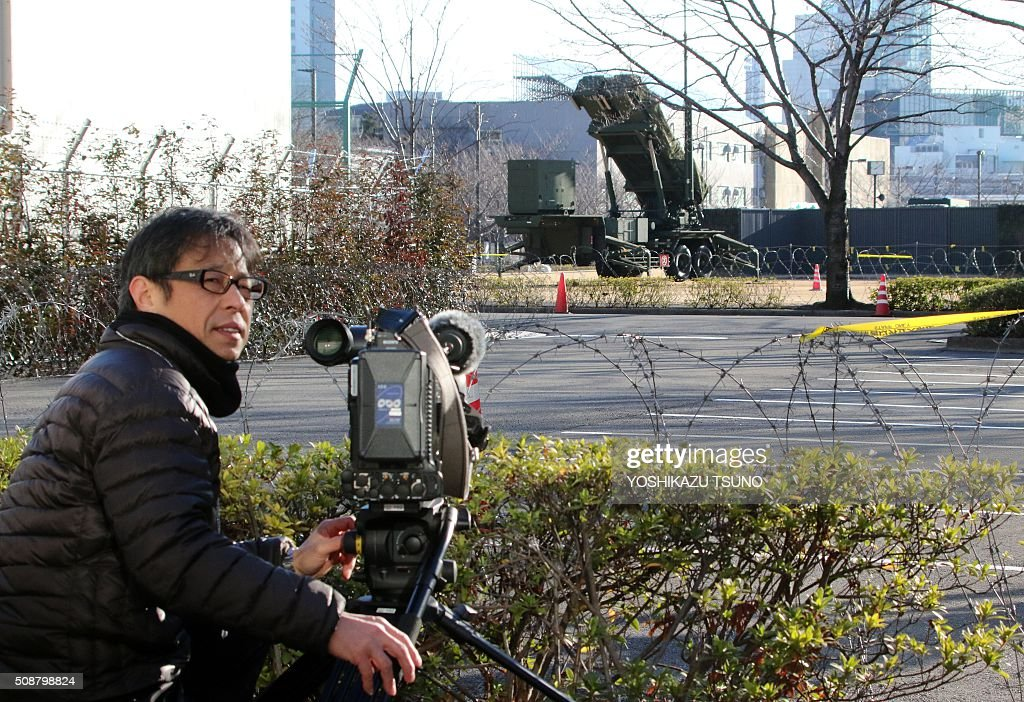 A TV cameraman video records footage of a Japanese Self-Defense Force Patriot Advanced Capability-3 (PAC-3) interceptor launcher deployed at Defence Ministry headquarters in Tokyo on February 7, 2016. North Korea launched a long-range rocket on February 7, violating UN resolutions and doubling down against an international community already determined to punish Pyongyang for a nuclear test last month. AFP PHOTO / Yoshikazu TSUNO / AFP / YOSHIKAZU TSUNO