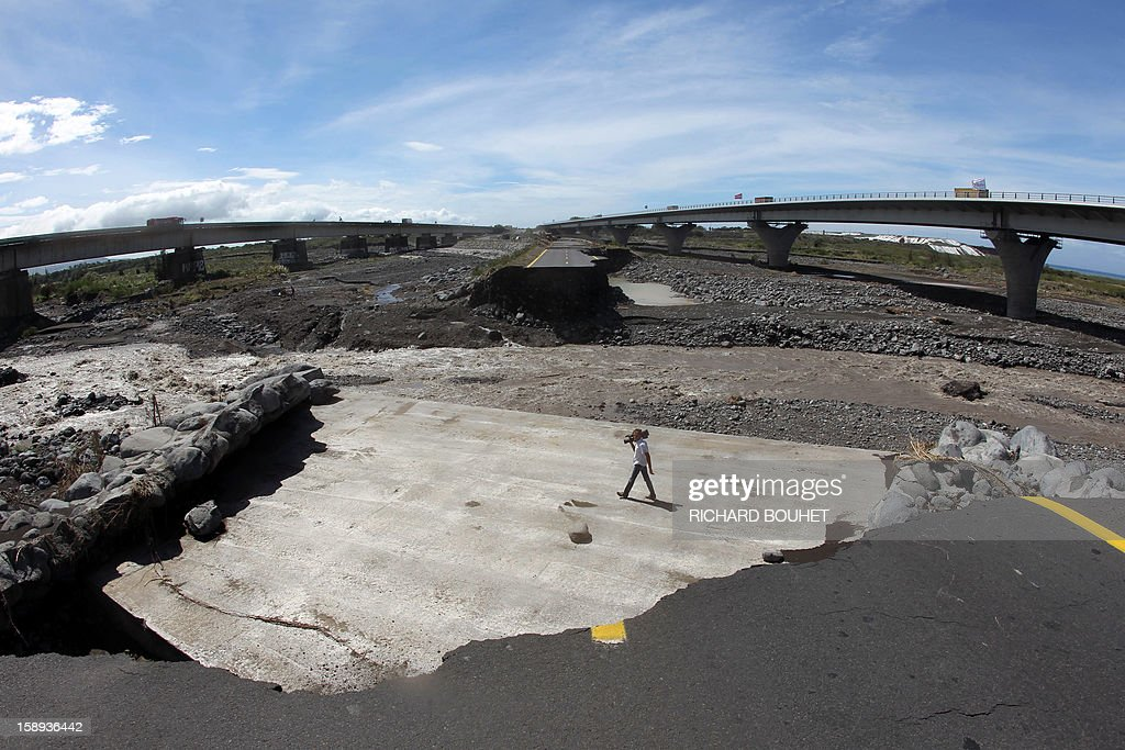 A cameraman walks between two remaining pieces of road crossing the river that links Saint Louis de la Reunion with Saint Pierre on January 4, 2013 near Saint Louis, on the French island of La Reunion, following the passing of cyclone Dumile. Winds of up to 180 kilometres per hour (110 miles per hour) and torrential rain caused extensive damage to the electricity network after cyclone Dumile passed within 90 kilometres of the island's west coast at around 0900 GMT.