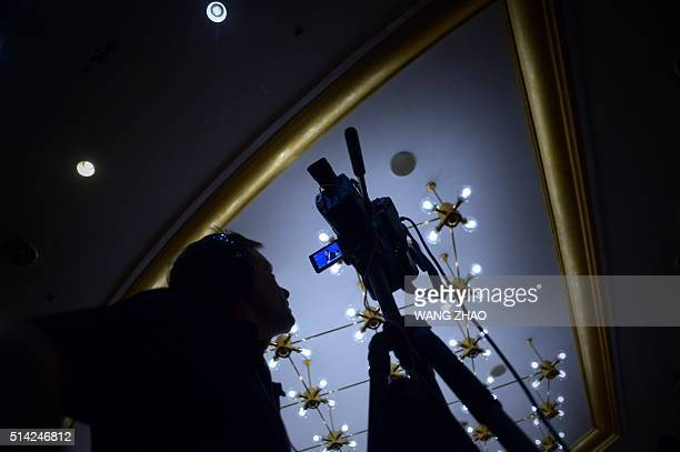 A cameraman watches as Chinese Foreign Minister Wang Yi speaks during a press conference at the National People's Congress in Beijing on March 8 2016...