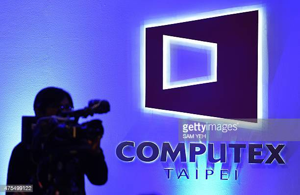 A cameraman works in front of a logo of the Computex tech trade show at the World Trade Center in Taipei on June 1 2015 Smart living and wearable...