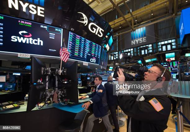 A cameraman works on the floor at the closing bell of the Dow Industrial Average at the New York Stock Exchange on October 6 2017 in New York Wall...