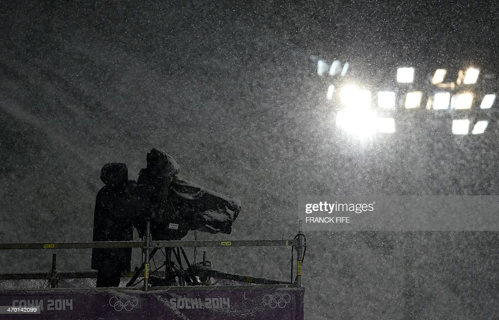 A TV cameraman works under heavy snowfall during the Men's Freestyle Skiing Halfpipe finals at the Rosa Khutor Extreme Park during the Sochi Winter Olympics on February 18, 2014. AFP PHOTO / FRANCK FIFE