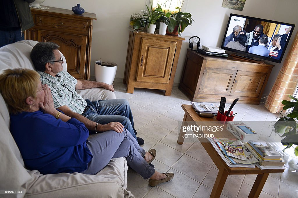 Cameramen film French Christian Larribe, brother of former French hostage Daniel Larribe, and his wife, as they watch on a TV set, the four French hostages' arrival in France, on October 30, 2013 in Espeluche, southern France. Daniel Larribe, Marc Feret, Pierre Legrand and Thierry Dol, who were kidnapped by Al-Qaeda in the Islamic Maghreb in northern Niger in 2010, have been released on October 29. Daniel Larribe was working for French nuclear giant Areva when he was kidnapped with the others on September 16, 2010, from a uranium compound in Arlit, north-central Niger.