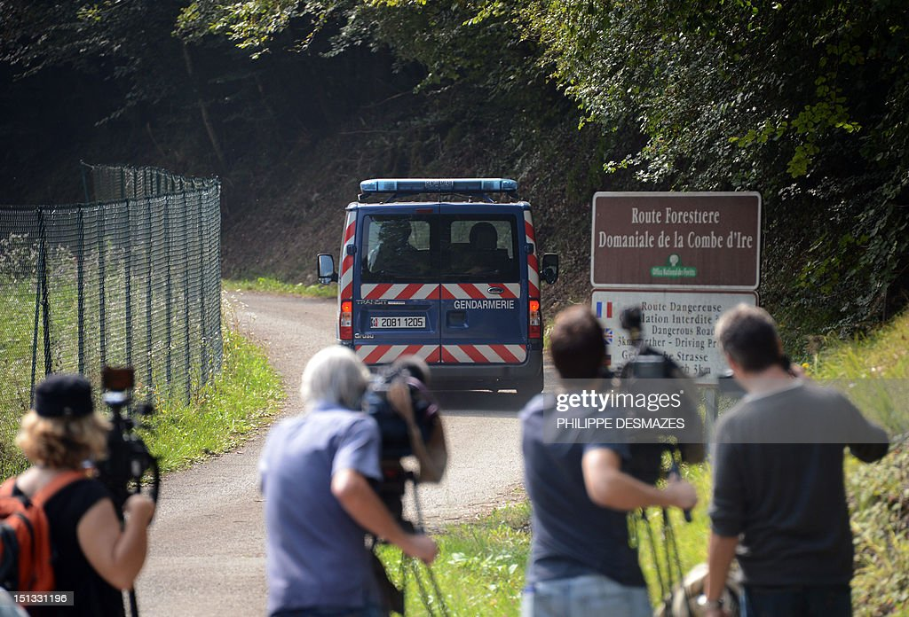 Cameramen grab a truck of french gendarmes on the 'Combe d'Ire' road in the French Alpine village of Chevaline on September 6, 2012, where four people were shot dead. A four-year-old girl spent hours curled up under her mother's body and miraculously survived the deadly attack that left her father, mother and grandmother dead and her elder sister seriously injured, officials said.